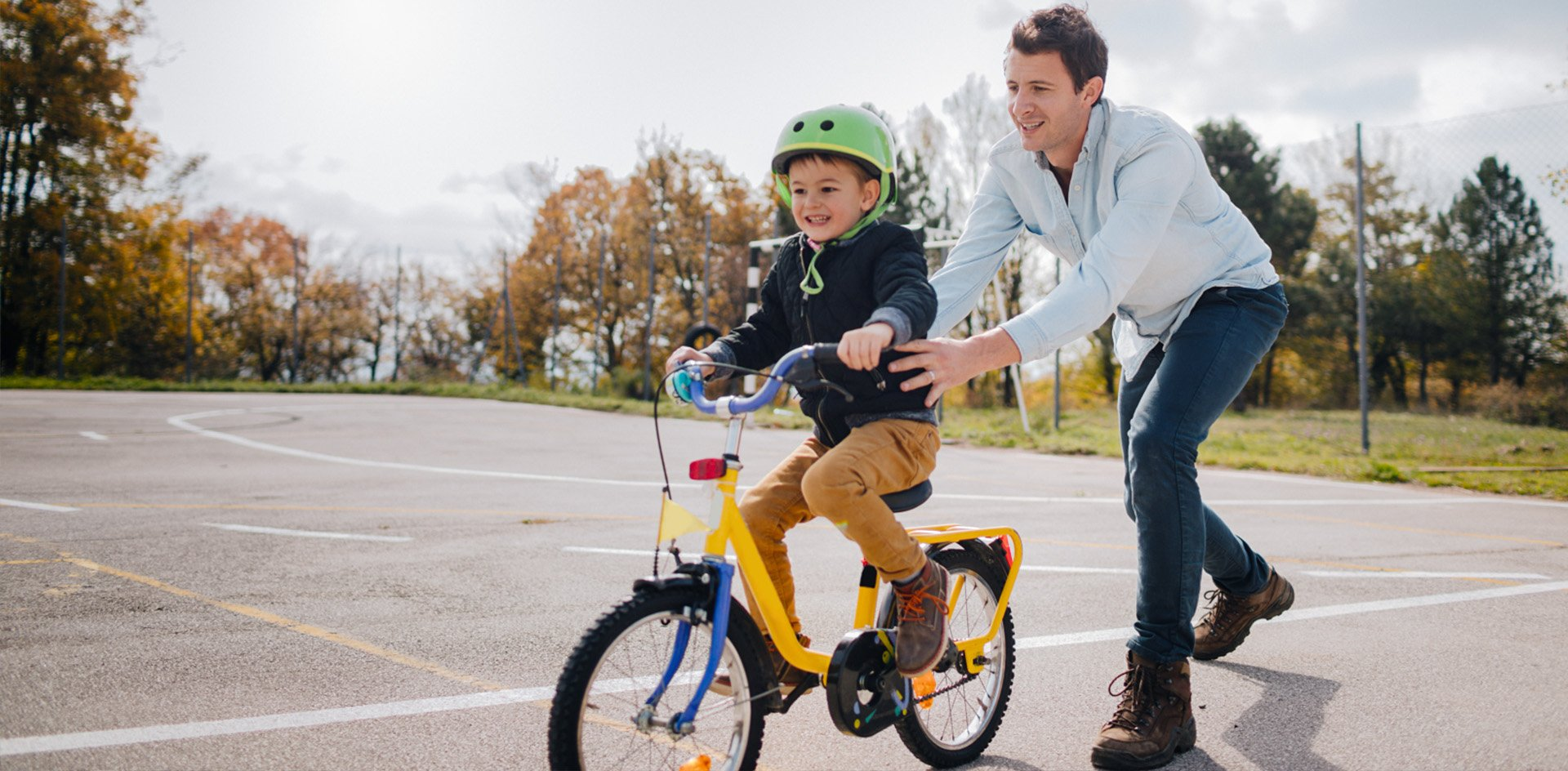 Dad helping son ride a bike