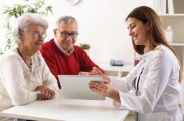Picture of senior couple talking with clinician and looking at computer
